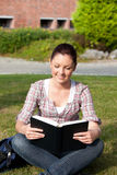Relaxed female student reading a book outdoors Royalty Free Stock Image
