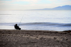 Relaxed fisherman fishing on the beach Royalty Free Stock Photography