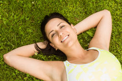 Relaxed fit brown hair lying on grass Royalty Free Stock Photography