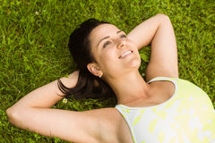 Relaxed fit brunette lying on grass Royalty Free Stock Photo