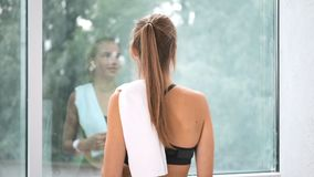 Relaxed fitness girl smiling approaching to big glass window admiring nature back view