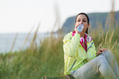 Relaxed fitness woman drinking water on workout rest. Relaxed fitness woman drinking water from bottle on a workout break at beach on summer morning. Sporty girl Stock Photo