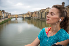 Relaxed fitness woman listening music in front of ponte vecchio Royalty Free Stock Photos