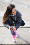 Relaxed fitness woman listening music on smartphone Royalty Free Stock Images