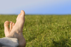 Relaxed foot. On green grass stock photos