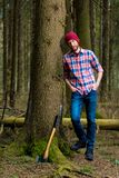Relaxed forester resting with an ax. Leaning against a tree Stock Image