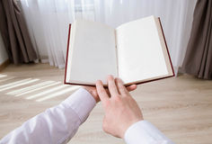 Relaxed gentleman holding an opened  book. At home Royalty Free Stock Images