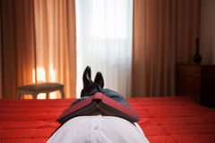 Relaxed gentleman lying on the bed with book with a red cover Royalty Free Stock Photos