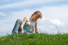 Relaxed girl. The red girl has a rest at top of a hill, sitting in a grass stock image