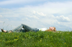 Relaxed girl. The red girl has a rest at top of a hill, lays in a grass stock image