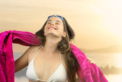 Relaxed girl in beachwear with swimming goggles  against beach a Royalty Free Stock Photo