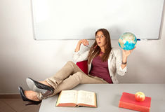 Relaxed girl in classroom holding globe Stock Photos