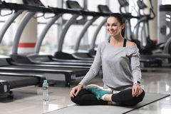 Relaxed girl doing a yoga posture after training. Keep calm. Delighted happy young girl enjoying yoga and doing lotus posture after having training Royalty Free Stock Photo
