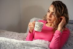 Relaxed girl drink coffee on a comfortable couch. At home Royalty Free Stock Photography