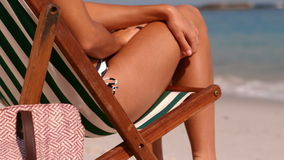 Relaxed girl lying in the deck chair looking the horizon. In slow motion stock footage
