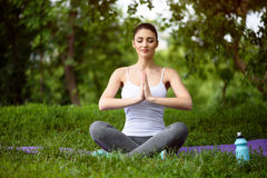 Relaxed girl meditating in park. Peaceful young woman is doing yoga in the nature. She is sitting and joining her hands together. Her eyes are closed with Royalty Free Stock Photo