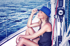 Relaxed girl on sailboat. Relaxed girl with closed eyes of pleasure sitting on sailboat, enjoying mild sunlight, fashion model in luxury sea cruise, summer royalty free stock photography