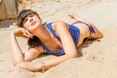 Relaxed girl on a sandy beach for sunbathing Stock Images
