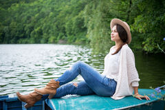 Relaxed girl sitting in a boat on a lake Royalty Free Stock Image