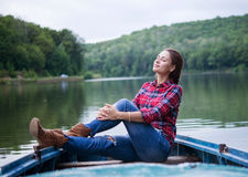 Relaxed girl sitting in a boat on a lake Stock Photos