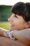 Relaxed girl smiling. Young relaxed female sitting at a table and looking upwards Stock Image