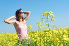 Relaxed girl on sunny flower field. Stock Photos