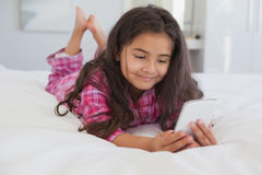 Relaxed girl text messaging in bed Royalty Free Stock Images
