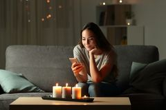 Relaxed girl using phone in the night with candle lights. Sitting on a couch in the living room at home Royalty Free Stock Photography