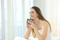 Relaxed girl waking up having breakfast on the bed Stock Photography