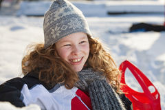 Relaxed girl in winter cloths with red sledge. Blond teenager girl sitting on a bench in a snowy park Royalty Free Stock Image