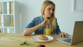 Relaxed girl working during breakfast stock video