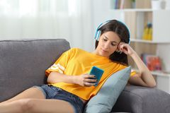 Relaxed girl in yellow listening to music at home. Relaxed girl in yellow listening to music sitting on a couch in the living room at home Stock Image