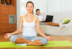 Relaxed girl in yoga position and lazy guy Stock Photo