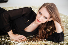 Relaxed gorgeous young woman with sequins on her hair Stock Photo