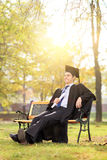 Relaxed graduate sitting on a bench in park. In autumn Royalty Free Stock Images