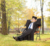 Relaxed graduate student sitting on a bench in park Stock Photography