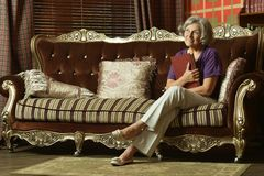Relaxed grandmother sitting Royalty Free Stock Photos