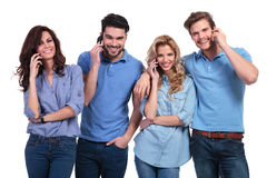 Relaxed group of casual people talking on their cell phones Royalty Free Stock Photo