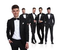 Relaxed group leader of groomsmen stands in front and smiles royalty free stock photo