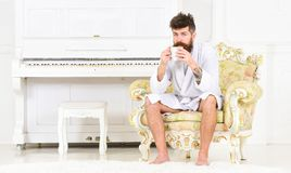 Relaxed guy drinking tea or coffee. Rich businessman in white hotel room. Serene morning before work. Relaxed bearded man drinking tea or coffee. Rich royalty free stock photos