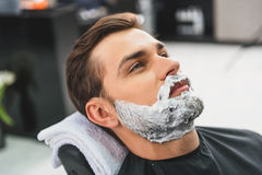Relaxed guy having facial treatment at hairdressers Royalty Free Stock Image