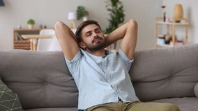 Millennial man resting on couch spending lazy weekend at home
