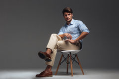 Relaxed handsome man in blue shirt sitting on the chair Stock Photography