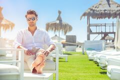Relaxed handsome man sitting on white chairs during summer at the beach. White shirt and sunglasses. Legs stretched out