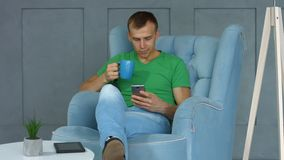 Handsome man with phone sitting in armchair at home stock video