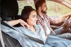 Relaxed and happy couple are sitting together and riding in car. They are using the seatbelts. Guy is driving while girl royalty free stock image