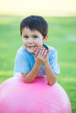 Relaxed happy hispanic boy portrait outdoor. Portrait young cute hispanic boy happy relaxed smiling, leaning on pink exercise ball outdoor, blurred background Royalty Free Stock Photos