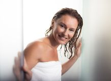 Cheerful middle aged woman standing at shower door. Relaxed and happy. Portrait of beautiful lady with wet hair walking out from bathroom. She is wearing soft stock photography