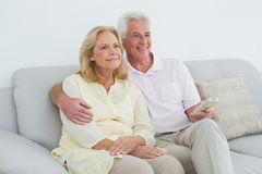 Relaxed happy senior couple with remote control Stock Images