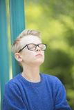 Relaxed happy teenage boy portrait. Portrait thoughtful and relaxed young blond teenage boy outdoor with glasses and closed eyes, concentrated and meditating Stock Photos